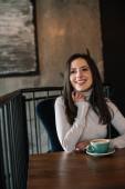 usmívající se mladá žena sedí u dřevěného stolu s cappuccino na balkóně v kavárně