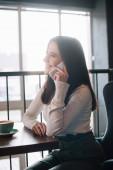Lächelnde junge Frau sitzt mit Cappuccino am Holztisch und plaudert auf dem Balkon im Café auf dem Smartphone