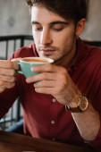 dreamy sad young man sitting at wooden table with cappuccino in coffee shop