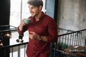 mosolygós férfi áll az erkélyen cappuccino a kávézóban