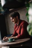 mosolygós fiatal szabadúszó dolgozik laptop kávézóban