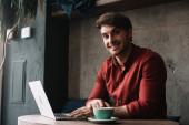 mosolygós fiatal szabadúszó dolgozik laptop és kávézó