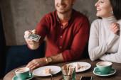 abgeschnittene Ansicht eines jungen Paares, das Käsekuchen isst und Kaffee trinkt, während der Mann Geld im Café hält