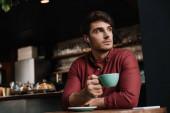 zamyšlený muž v bezdrátových sluchátkách pije kávu v kavárně