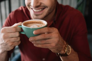 cropped view of smiling young man with cup of tasty cappuccino in coffee shop