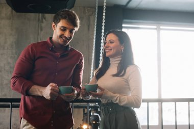 happy couple talking while drinking coffee on balcony in coffee shop