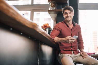 smiling handsome man sitting near bar counter in wireless earphones using smartphone