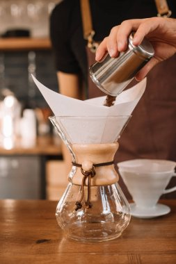 partial view of barista preparing filtered coffee using chemex