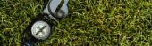 panoramic shot of retro compass on green grass