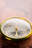 close up of vintage compass with golden arrow