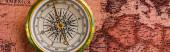 panoramic shot of golden compass near map