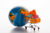 Photo toy shopping cart with shopping bags near globe on white, e-commerce concept