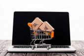 toy shopping cart with small carton boxes on laptop with blank screen isolated on white, e-commerce concept