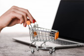 cropped view of woman holding toy shopping cart near laptop isolated on white, e-commerce concept