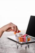 Fotografie oříznutý pohled na ženu držící nákupní košík s malými nákupními taškami v blízkosti notebooku izolovaného na bílém, e-commerce konceptu