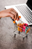 cropped view of woman holding toy shopping cart with small shopping bags near laptop, e-commerce concept
