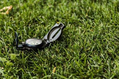 Selective focus of retro compass on green grass stock vector