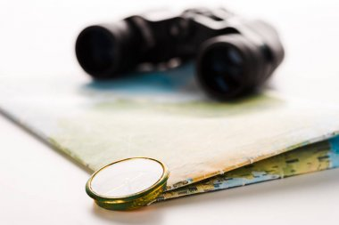 selective focus of golden compass near map and binoculars on white