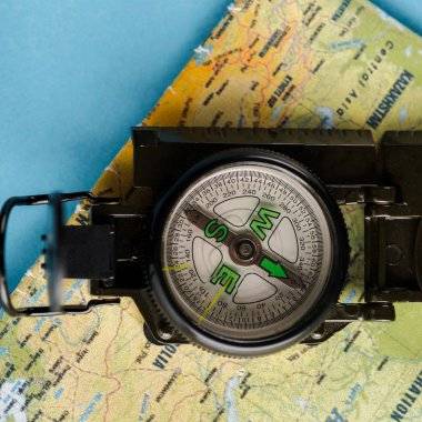 close up of black compass near map on blue