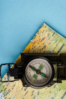 top view of retro and black compass on map on blue