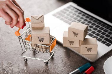 cropped view of woman holding toy shopping cart with small boxes near laptop, e-commerce concept