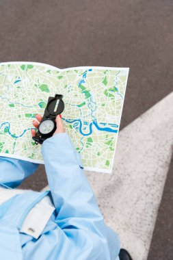 selective focus of woman holding map and compass on street