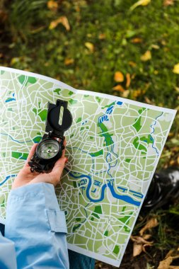 cropped view of woman holding map and vintage compass outside
