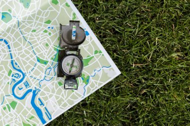 top view of vintage compass on map on grass