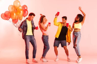 happy multicultural friends holding plastic cups and gesturing while dancing on pink