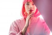 attraktive Frau, die Lippen berührt und in die Kamera auf weiß und rosa schaut