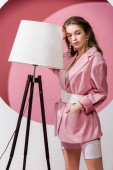 beautiful girl standing with hand in pocket near floor lamp on white and pink