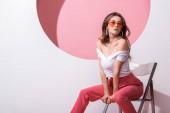 attraktive Frau mit Sonnenbrille sitzt auf Stuhl auf weiß und rosa
