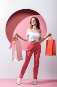 cheerful woman in sunglasses holding shopping bags on pink and white