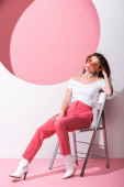 stylish woman sitting on chair on pink and white