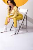 atraktivní a stylová žena v slunečních brýlích sedí na židli na bílém