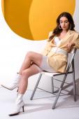 stylová mladá žena sedící na židli na bílém a oranžovém