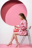 attraktives Mädchen berührt Verbeugung auf Geschenk, während es auf weiß und rosa sitzt