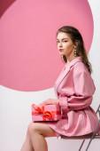 vonzó lány gazdaság ajándék doboz, miközben ül a fehér és rózsaszín
