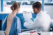 Selektiver Fokus des Allergologen hält Klemmbrett in der Nähe von Frau mit markiertem Rücken