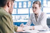 Fotografie selektivní zaměření atraktivní alergolog držící stříkačku poblíž člověka na klinice