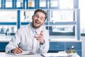 veselý lékař v brýlích a bílém plášti sedí za stolem a gestikuluje na klinice