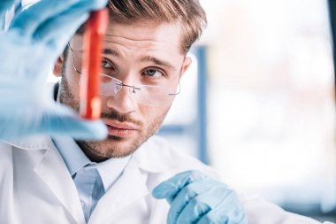 selective focus of handsome immunologist in glasses holding test tube with red liquid in clinic