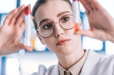 Selective focus of attractive immunologist in glasses looking at test tubes stock vector