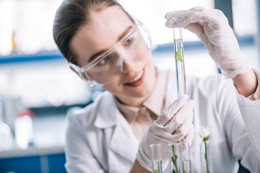 selective focus of cheerful biochemist in goggles holding test tube with small green plant