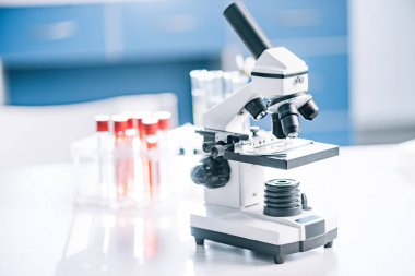 selective focus of modern microscope near test tubes with samples
