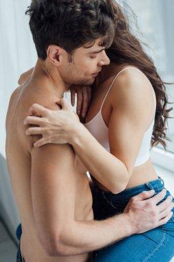 Shirtless man hugging girlfriend sitting on windowsill stock vector