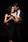 bearded man and attractive girl holding glasses with red wine isolated on black