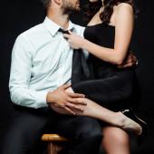 abgeschnittene Ansicht eines bärtigen Mannes, der auf einem Stuhl sitzt und sexy Mädchen in einem Kleid berührt, das auf schwarz isoliert ist