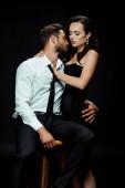atraktivní žena dotýká vousatý přítel v košili sedí na židli izolované na černé