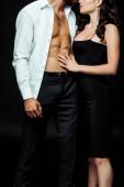 Fotografie Ausgeschnittene Ansicht einer jungen Frau, die einen muskulösen Mann im schwarzen Hemd berührt